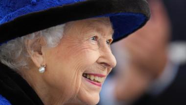 Elisabeta a II-a, din profil, cu pălărie albastră, zâmbește