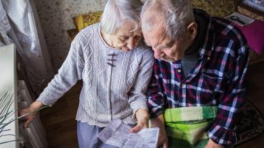 doi batrani se uita la o factura cu mana pe calorifer