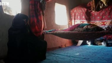 o femeie si un bebelus intr-o casa saraca din afganistan