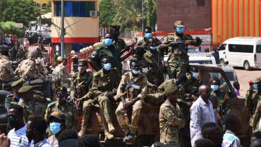 Soldați stau pe un vehicul și privesc spre protestatari în Sudan