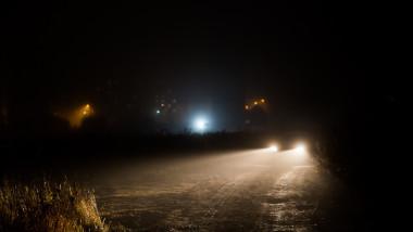 car headlight cones in night fog at field behind city