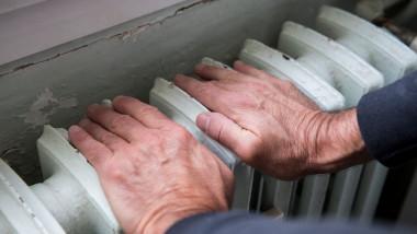 O persoană în vârstă ține mâinile pe calorifer.