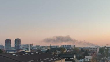 fum de la deseuri arse, observat peste cladirile din bucuresti, la mare distanta de oras