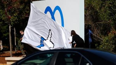 un angajat dezveleste un panou pe care este desenat noul logo al companiei Facebook