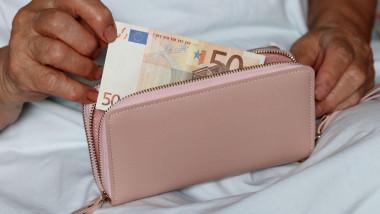 femeie care scoate o bancnota de 50 de euro din portofel