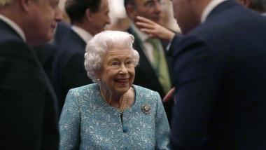 regina elisabeta a II-a razand in timp ce vorbeste cu un invitat