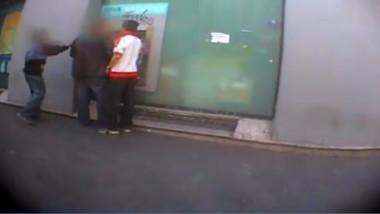 copii care stau langa un barbat care este langa un bancomat