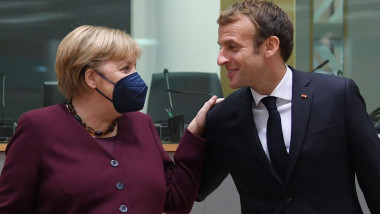 Germany's Chancellor Angela Merkel (L) speaks with France's President Emmanuel Macron on the second day of a European Union (EU) summit at The European Council Building in Brussels on October 22, 2021
