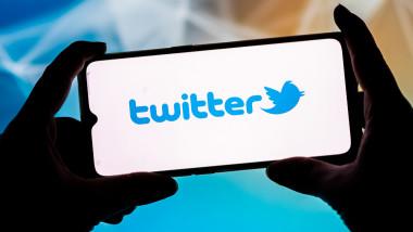 logo twitter pe ecranul unui telefon mobil tinut în maini de o persoana