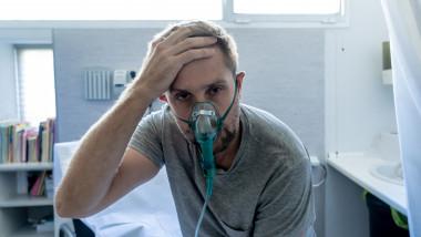 pacient cu masca de oxigen sta in sezut cu mana la cap