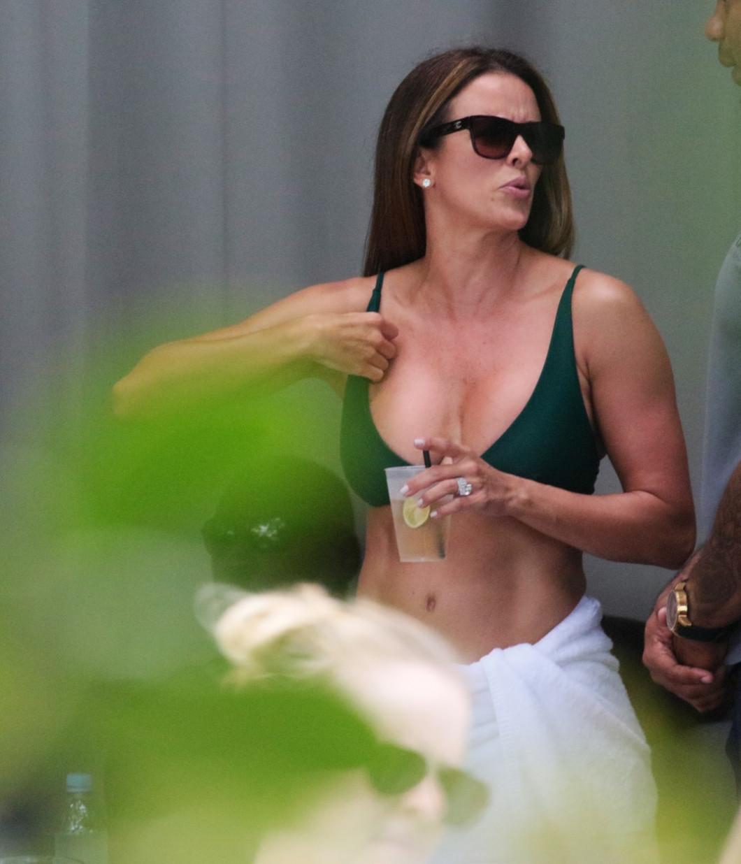 EXCLUSIVE: Michael Jordan smokes a cigar while his wife dancings in a green bikini at a pool party in Miami