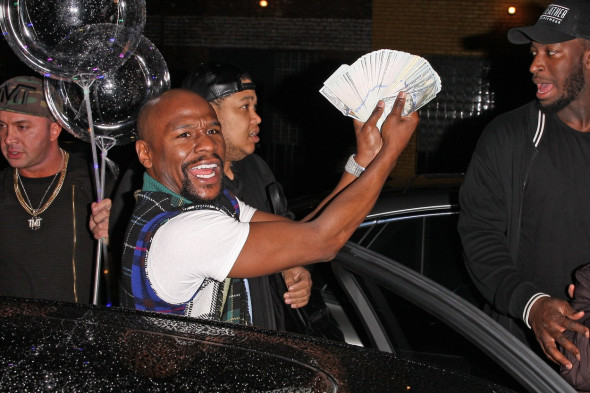 EXCLUSIVE: Promoter Floyd Mayweather flashes his money as he leaves TAO restaurant with his entourage