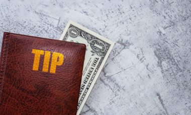 Dollar bill lying in the cover with the inscription: Tip. One dollar in a folder. Tip concept. Flat lay