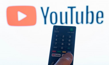 A man points a remote control at a smart television displaying the YouTube app in a bedroom at home in the UK. November 2018.