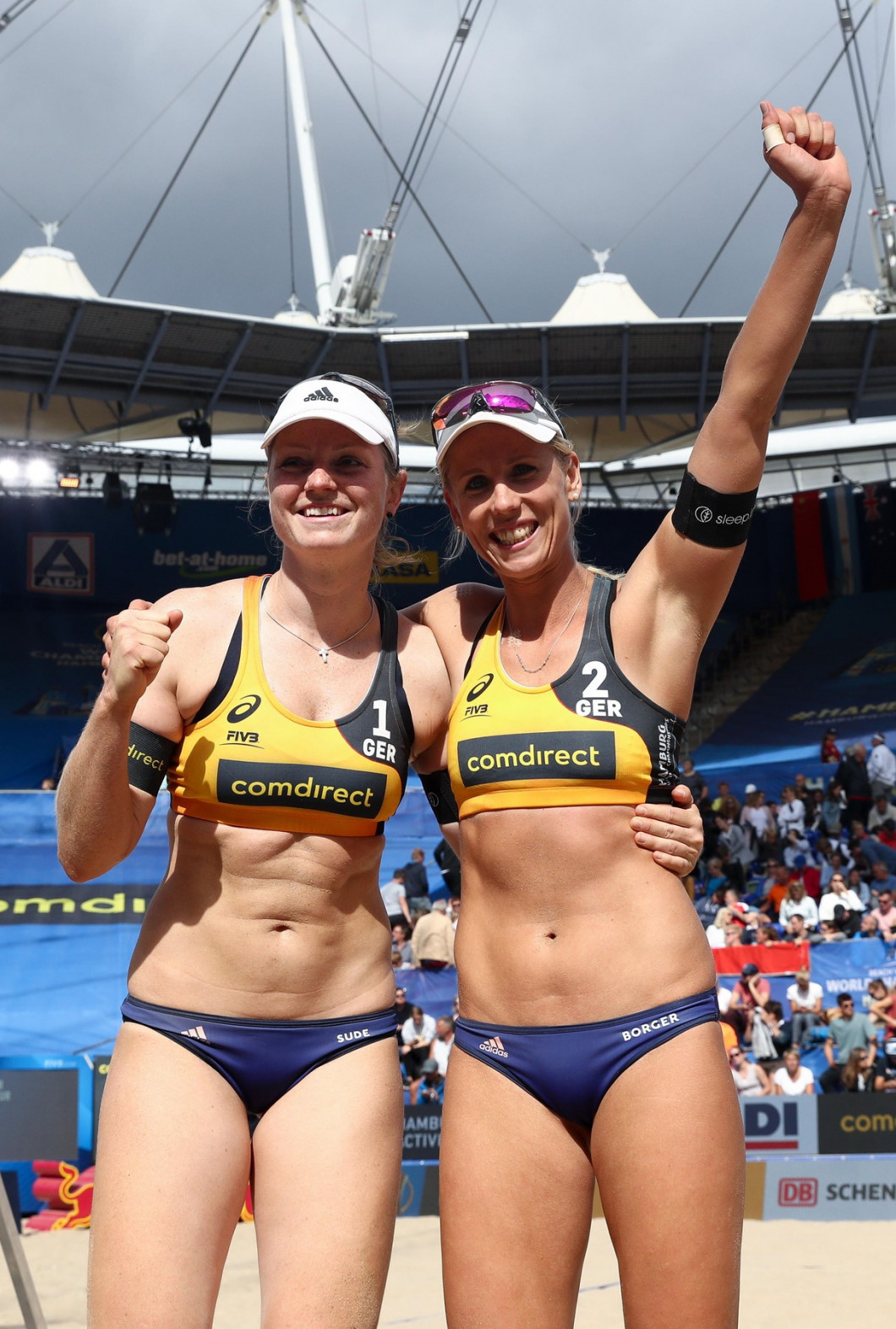 03 July 2019, Hamburg: Beach Volleyball, World Championship, at Rothenbaum Stadium: Round of 32, Women. Borger/Sude (Germany) - Behrens/Tillmann (Germany). Karla Borger and Julia Sude (l) are happy about their victory on the Center Court. Photo: Christian