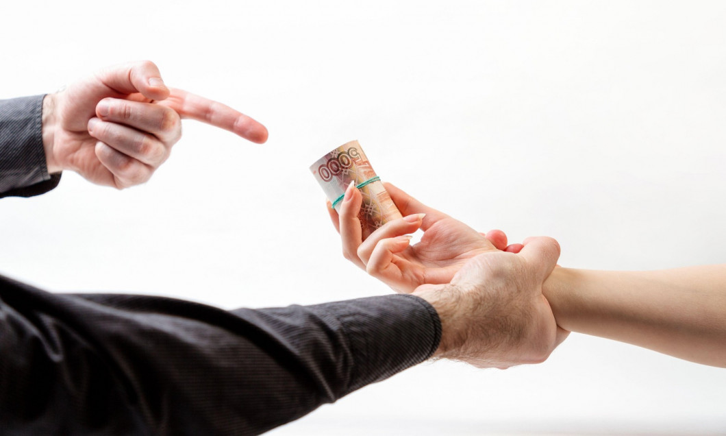 Bribery. A man's hand in a black shirt catches a woman's hand with a bribe. Side view. White background. The concept of the world anti-corruption day.