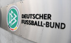 "15 January 2021, Hessen, Frankfurt/Main: The logo ""DFB"" and the lettering ""Deutscher Fuball-Bund"" are emblazoned on a wall in front of the main entrance to the DFB headquarters. In the inner circle of the crisis-ridden association, the power struggle betw"