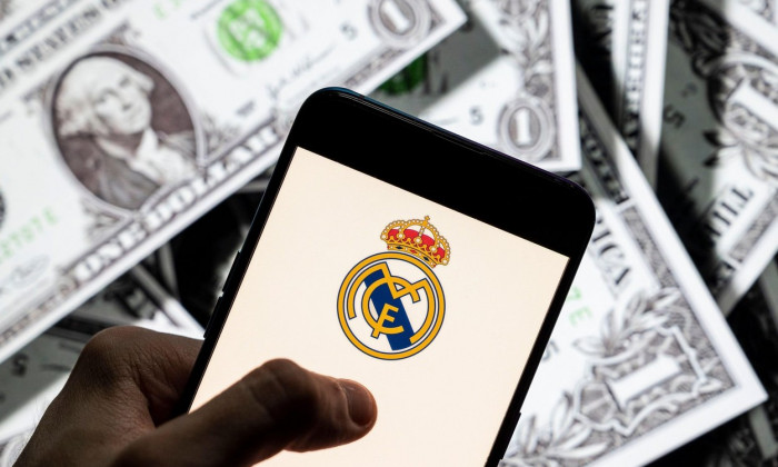 In this photo illustration Spanish professional football club team Real Madrid Club de Ftbol commonly known as Real Madrid logo seen on an Android mobile device screen with the currency of the United States dollar icon, $ icon symbol in the background.