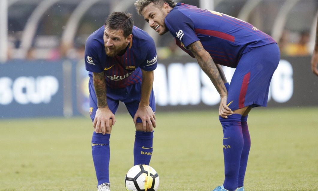 Lionel Messi and Neymar of Barcelona stand on the field