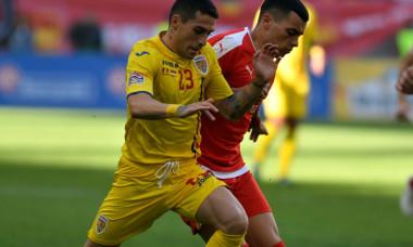 Nicolae Stanciu într-un duel pentru balon, în meciul cu Serbia