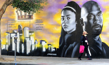 EXCLUSIVE: A Woman wearing a mask walks by Kobe Bryant Mural in Los Angeles as Coronavirus Epidemic Numbers Soar