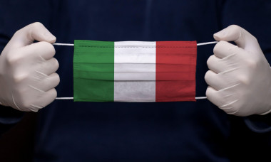 Health employee doctor holding medical face mask with Italy flag. Coronavirus (COVID-19) pandemic affects the country.