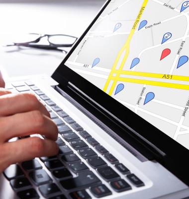 persoana care tasteaza la laptop si are o harta in fata care foloseste gps