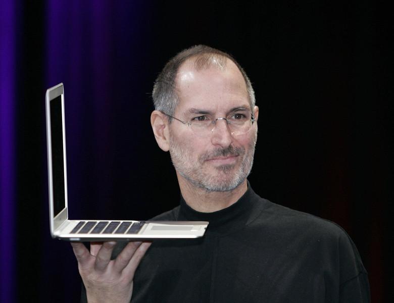 steve jobs, cofondatorul apple, cu un laptop in mana in timpul unei prezentari