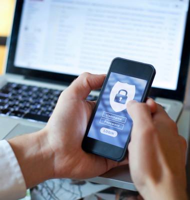 barbat cu telefon in mana incercand sa-si introduca o parola pe un ecran albastru cu un laptop in spate