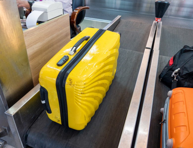 Yellow large luggage on belt at counter airline