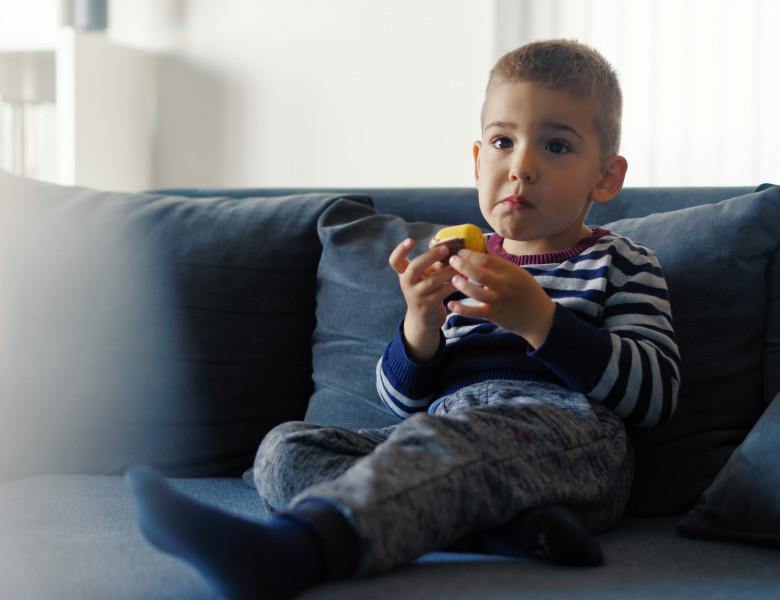 copil care mananca in fata televizorului