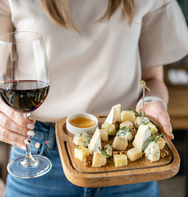 Girl,Holding,Glass,Red,Wine,And,Wooden,Plate,With,Cheese.