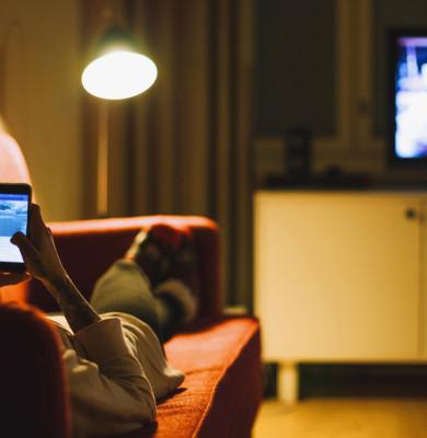 Femeie se uită la telefonul mobil în timp ce merge televizorul