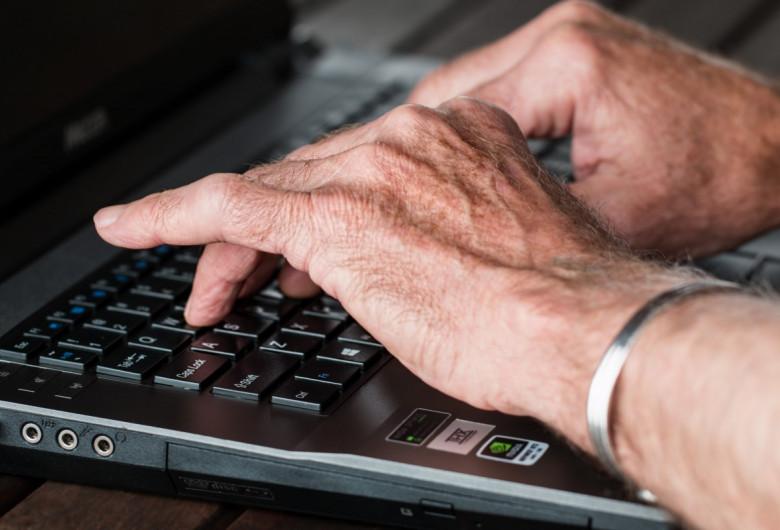 Bătrân cu laptop, mâini de vârstnic lucrează la calculator, internet
