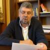 Marcel Ciolacu, citește de pe foi lângă o bibliotecă
