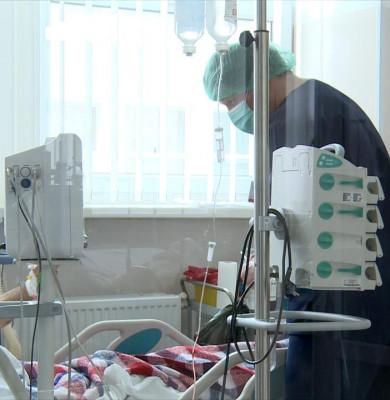 Pacient pe pat de spital cu doctor lângă el