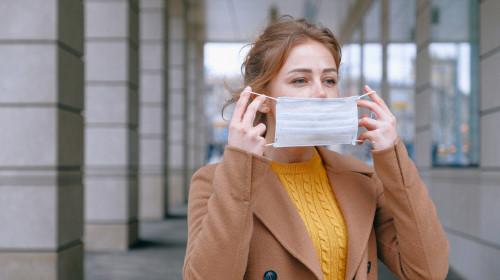 Femeie își pune masca sanitară pe față, de teama COVID-19, coronavirus