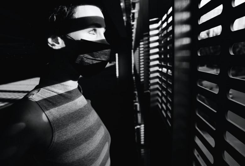 Bărbat cu mască sanitară pe față stând în casă în autoizolare pentru COVID-19, coronavirus
