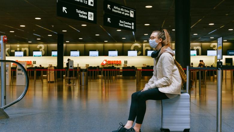 Femeie stă pe bagaj cu masca sanitară pe față, călătorie, turism în vremea COVID-19, coronavirus, aeroport
