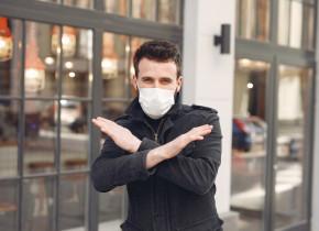 Bărbat tânăr cu mască sanitară pe față anti COVID-19, coronavirus, zâmbitor
