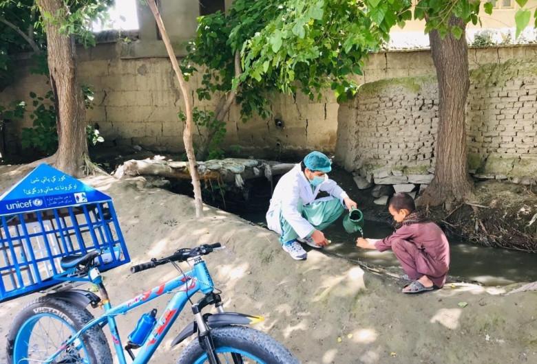 UNICEF, medic cu mască de protecție pe față toarnă apă unui copil sărac