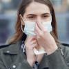 Femeie își pune mască de protecție pe față în pandemia de COVID-19, coronavirus