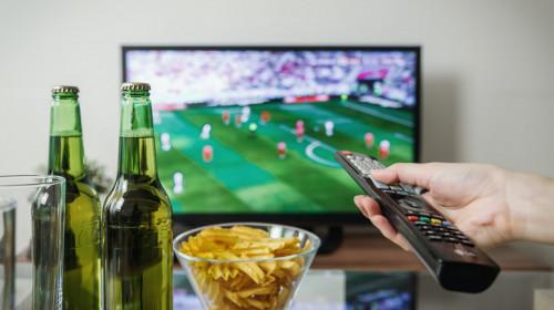 Meci de fotbal cu bere și chipsuri în fața televizorului și cu telecomandă, suporter