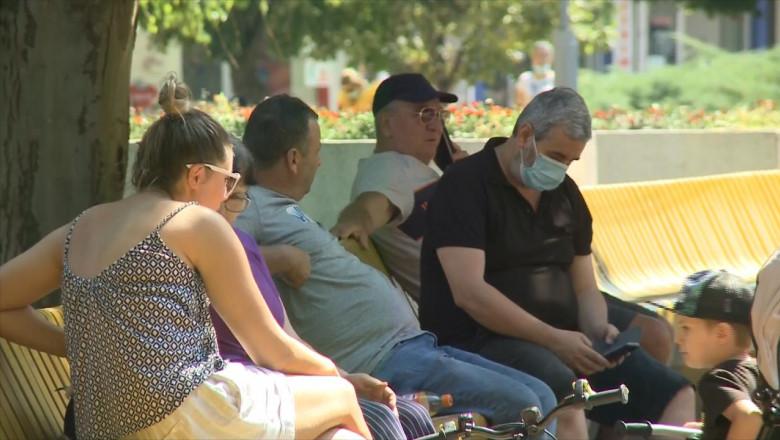 Oameni pe bancă, se relaxează în parc, unii cu mască alții fără