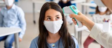 Elevă la clasă, cu profesoară care îi ia temperatura cu termoscaner, educație, mască de protecție, învățământ, ore, cursuri