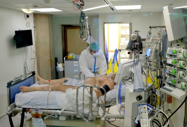 Pacient pe patul de spital, ventilat mecanic cu medic lângă el, tratat de COVID-19, coronavirus, SARS-CoV-2, ATI, terapie intensivă