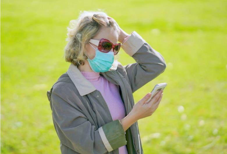 Femeie babă cu mască de coronavirus, COVID-19, SARS-CoV-2 se uită îngrijorată, temătoare în telefonul mobil la un SMS cu internet online, gadget