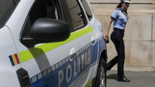 Polițistă lângă mașina de Poliție