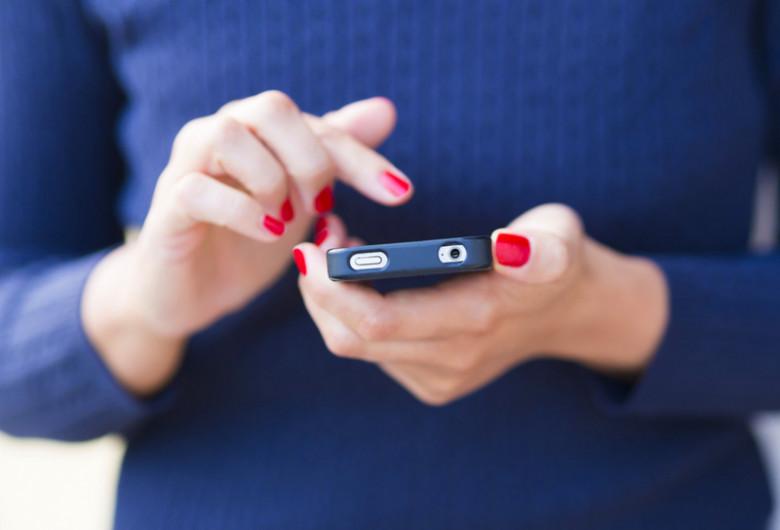 Femeie ține smartphone telefon mobil în mână, se uită pe Facebook, rețele de socializare, postează, internet, online, social media