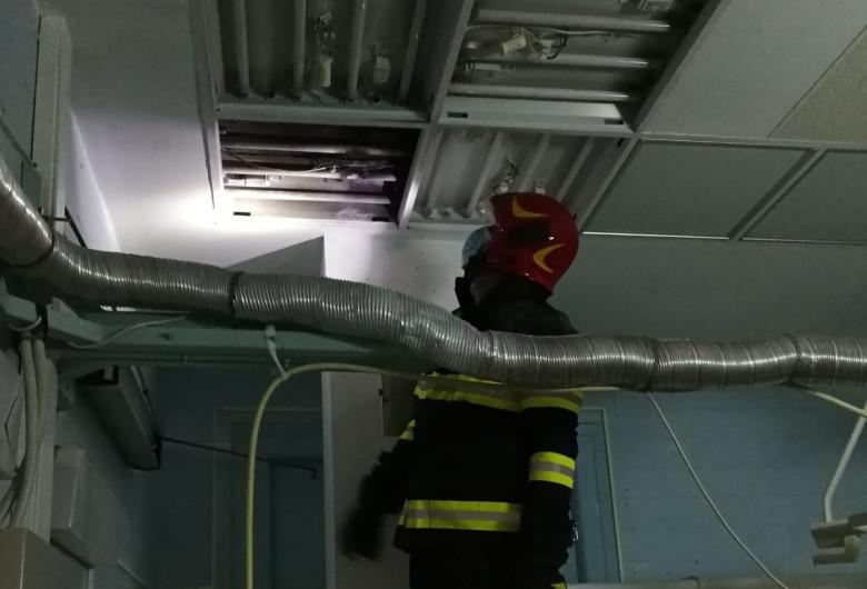Pompier se uită la un panou de iluminat care a luat foc la Spitalul Județean Cluj
